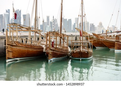 Traditional dhows with flags of Qatar are docked in harbor of Doha, such vessels are popular for tourist trips along the coast, Qatar, Middle East.