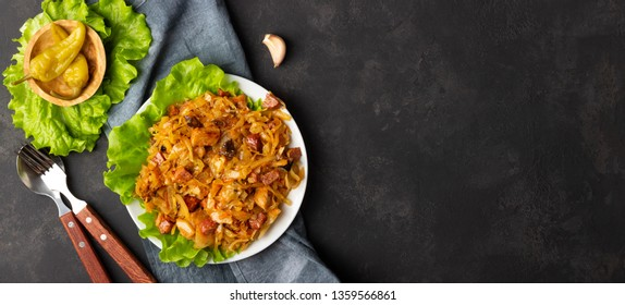 Traditional dish of polish cuisine - Bigos from fresh cabbage, meat and prunes. Top view with copy space.