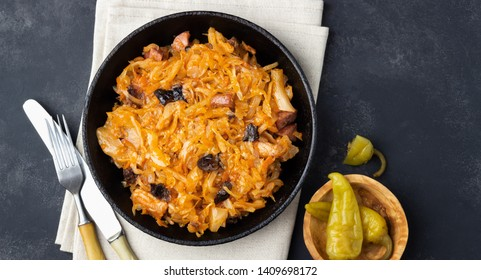 Traditional dish of polish cuisine - Bigos from fresh cabbage, meat and prunes. Top view. Dark background.