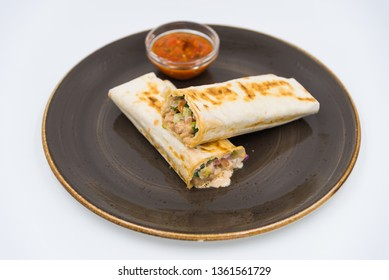 """Traditional dish """"Shaverma"""", cut on a plate with sauce."""