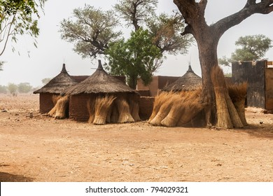 Traditional domestic huts in a african mosi village of Burkina Faso with some bundles of straw their circular walls.