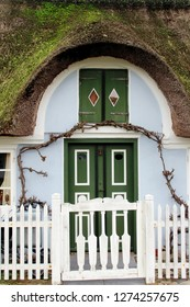 Traditional door of an old thatched house, white garden fence in the foreground, North Sea Island Fanoe, Denmark