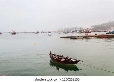 Traditional dorma boat anchored on Illa de Arousa fishing harbor under the fog
