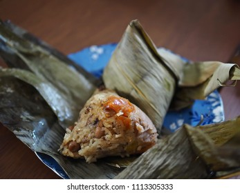 Traditional Dragon Boat Festival food concept unwrapping zongzi or rice dumpling in blue plate on wooden background. Asian food steamed sticky rice dumpling with fillings wrapped in reed leaves.