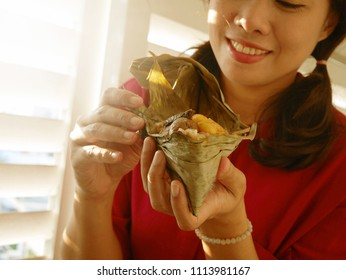 Traditional Dragon Boat Festival food concept Asian woman in red dress unwrapping zongzi or rice dumpling. Popular Asian food steamed sticky rice dumpling with fillings wrapped in bamboo, reed leaves.