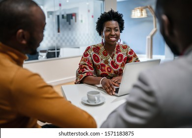 Traditional dressed black African business woman financial bank adviser in meeting with customer. African pattern