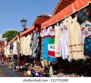 Traditional dresses and tourist souvenirs for sale at an outdoor market in Puebla, Mexico.