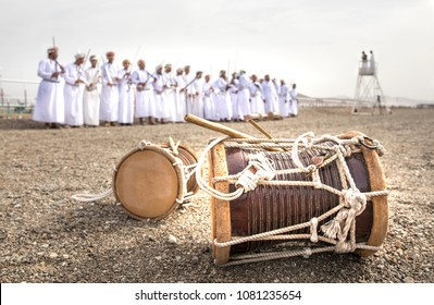 traditional drums on a ground with omani men lined up for traditional singing and dancing at the background