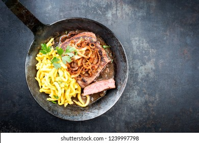 Traditional dry aged sliced roast beef with fried onion rings and Swabian spaetzle as top view in a wrough-iron pan with brown sauce with copy space