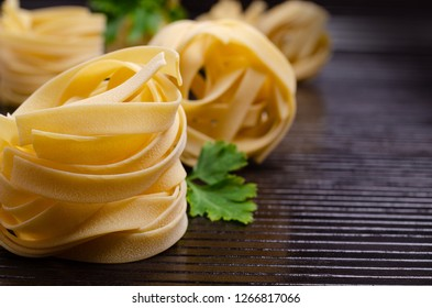 Traditional dry fettuccine pasta on dark wooden background. Selective focus.