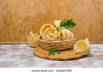 Traditional dry fettuccine pasta on brown wooden background. Selective focus.