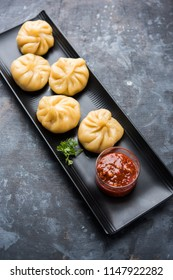 Traditional dumpling momos food from Nepal served with tomato chutney over moody background. Selective focus