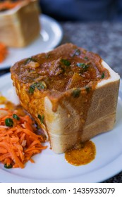 Traditional Durban Bunny Chow of bread filled with lamb curry with carrot salad served on the side at one of Durban's