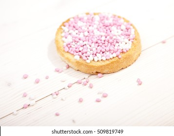Traditional Dutch birth celebration biscuit with pink muisjes on wooden background
