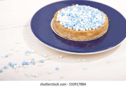 Traditional Dutch birth celebration biscuit with blue muisjes on wooden background