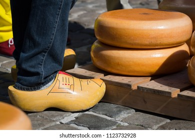 Traditional Dutch clogs and stacked cheeses at the Gouda cheese market, Netherlands