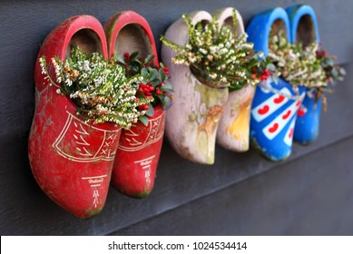 Traditional dutch clogs wooden shoes on wooden background. Family concept, father, mother and child
