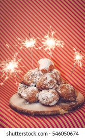 Traditional Dutch deep fried goods eaten on New Year's Eve in the Netherlands. With sparklers. Against a striped pink background