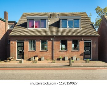 Traditional dutch duplex apartments with symmetrical facade from red bricks under tile roof with mansard windows (summer sunny day)