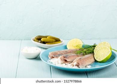 Traditional dutch food freshly salted herring fish with onion called hollandse nieuwe on turquoise plate and wooden background. European food concept with copy space.