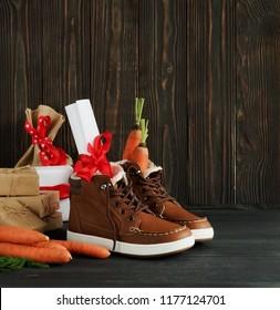 Traditional Dutch Holiday Saint Nicholas Sinterklaas background. Shoen Zetten. Zack van Sinterklaas.Children's shoes, carrots, gifts on brown  wooden background.  Copy space