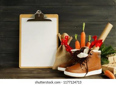 Traditional Dutch Holiday Saint Nicholas Sinterklaas background with mock up clipboard. Shoen Zetten. Zack van Sinterklaas. Children's shoes, carrots, gifts on brown wooden  background.  Copy space