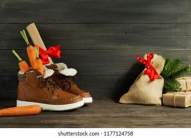 Traditional Dutch Holiday Sinterklaas background.Shoen Zetten. Zack van Sinterklaas.  Children's shoes, carrots, gifts on brown  wooden background.  Copy space