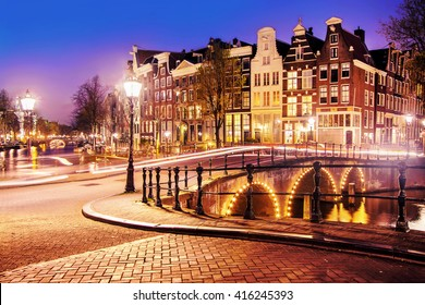 Traditional Dutch old houses and bridges on the canals in Amsterdam at night, The Netherlands