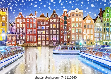Traditional Dutch old houses on canals in Amsterdam on a snowy winter night, The Netherlands