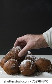 traditional Dutch oliebollen, oil dumpling or fritter, with wooden spoon, for New Year's Eve