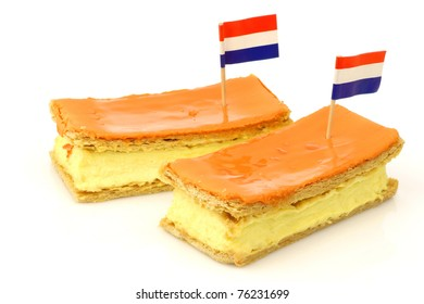 """Traditional Dutch pastry called """"tompouce"""" with a Dutch flag toothpick especially produced for  Queens day on april 30th in Holland on a white background"""