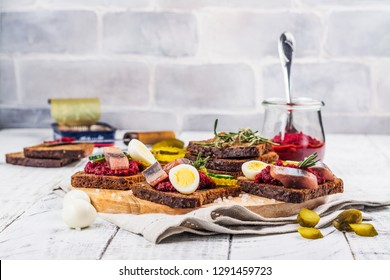 Traditional dutch sandwich smorrebrod with herring, beet root spread and pickled cucumbers