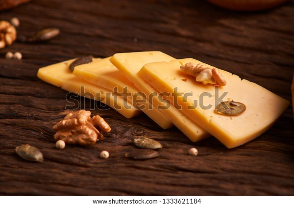 Traditional Dutch semi hard cheese served close up on rural table with sacking. Selective focus