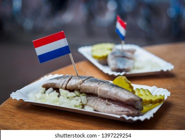 Traditional Dutch street food - saline herring with pickles, onions and Dutch flags in a fish. Still life with the Amsterdam snack in a soft focus.
