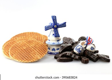traditional dutch syrup waffles and licorice candies with delftware isolated on white background