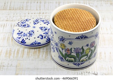 Traditional Dutch syrup waffles in an original Delftware container on wooden background