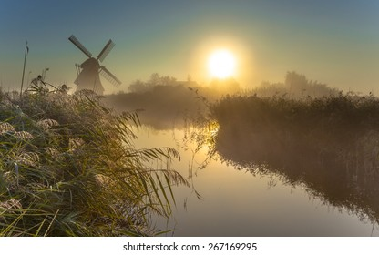 Traditional dutch Windmill in a dewy marshland area on a foggy morning in september
