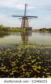 A traditional Dutch windmill in Kinderdijk Holland with a canal in front