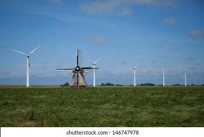 Traditional dutch windmill with modern wind turbines in the background. Old vs new