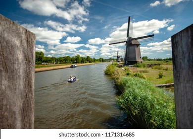Traditional Dutch windmill near the canal. Beautiful day along the city Alkmaar, Netherlands in summer. Travel Holland