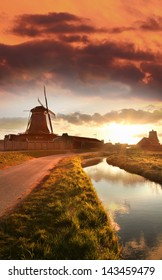 Traditional Dutch windmills with canal against sunset in Amsterdam area, Holland
