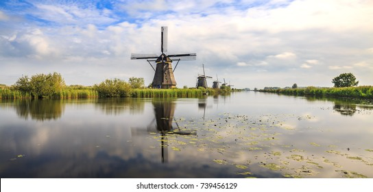 Traditional Dutch Windmills Kinderdijk, World Unesco heritage, during sunset late summer panorama. Reflection visible on the water surface.