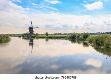 Traditional Dutch Windmills Kinderdijk, World Unesco heritage, on a sunny day late summer. Reflection visible on the water surface.