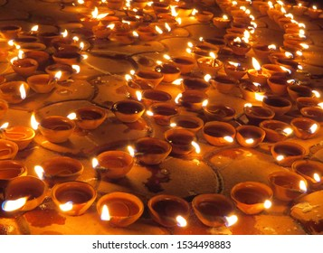 Traditional earthen lamps set on the floor for Diwali festival in India.