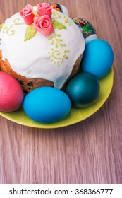 Traditional easter cake with glace icing  and colorful eggs on rustic table. Selective focus