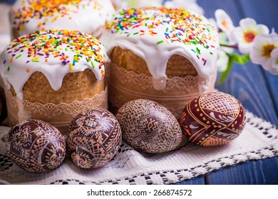 Traditional easter cake kulich Ukrainian Russian style with colored eggs on blue wooden background