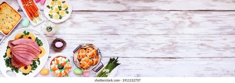 Traditional Easter ham dinner. Overhead view corner border on a white wood banner background with copy space. Ham, scalloped potatoes, vegetables, eggs, hot cross buns and carrot cake.