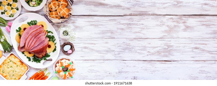 Traditional Easter ham dinner. Top down view side border on a white wood banner background with copy space. Ham, scalloped potatoes, eggs, hot cross buns, carrot cake and vegetables.