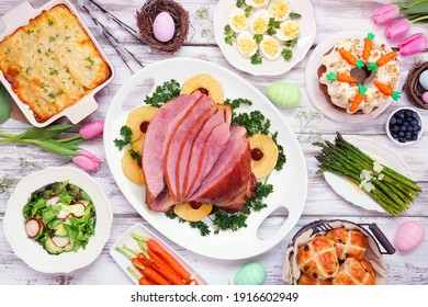 Traditional Easter ham dinner. Top view table scene on a white wood background. Ham, scalloped potatoes, eggs, hot cross buns, carrot cake and vegetables.