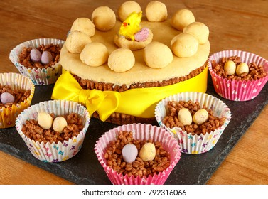 Traditional Easter holiday Simnel Cake surrounded by Chcoolate rice crispy nests